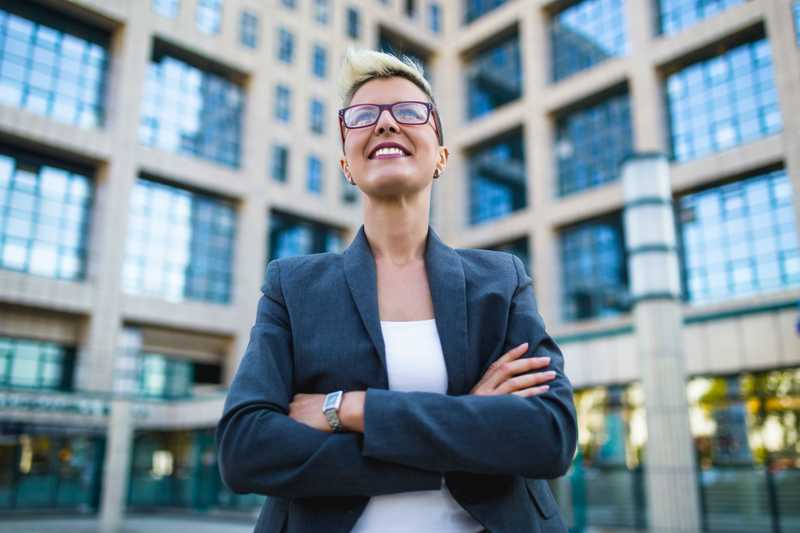A smiling woman in business wear standing in front of an urban building.