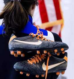 A pair of cleated shoes held over the shoulder of a woman in front of an American flag.
