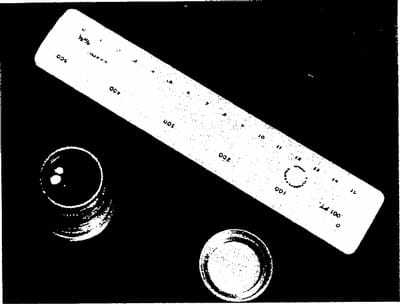 A black and white image of a ruler next to two glasses.