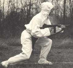 A CIA officer covered head to toe in a white suit, carrying a large gun.