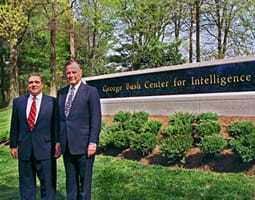 Two men in suits posing in front of the George Bush Center for Intelligence.