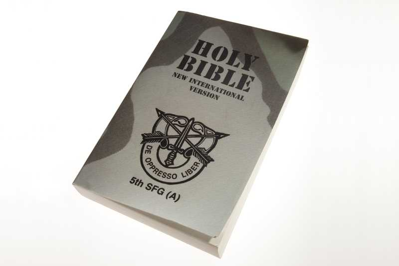 A Bible with a camouflage-print cover and the United States Army Special Forces insignia
