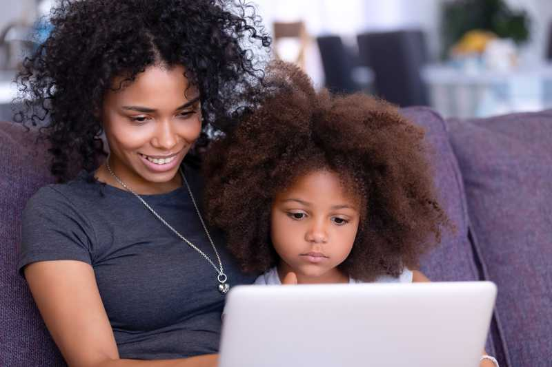 A mother and her young daughter sitting on a sofa looking at a computer.