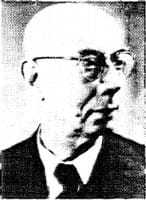 Closeup of a bald man with glasses looking to the right.
