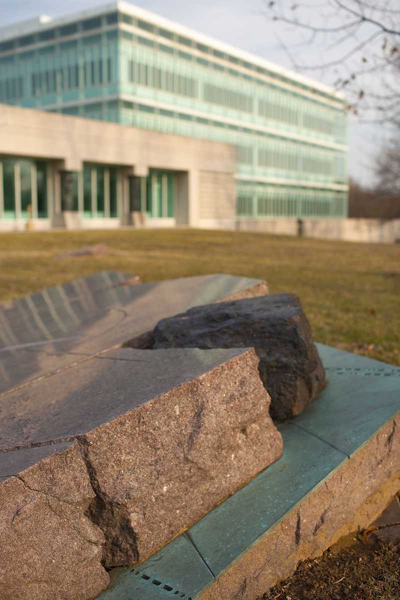 A dark boulder wedged in a divot on a glossed over plaque raised from the ground.