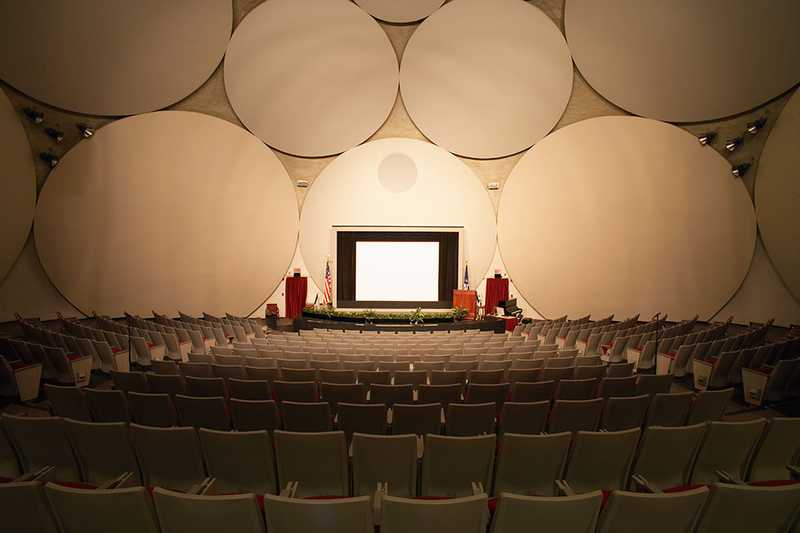 The theater inside the CIA Headquarters Auditorium, complete with a stage and large white disks to amplify sound.