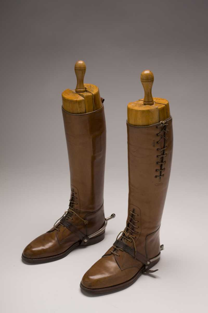 Tall brown leather boots with laces on the front and sides
