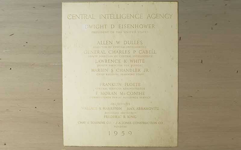 A rectangular, white, marble, cornerstone engraved with the names of officials responsible for creating the first CIA Headquarters Building.