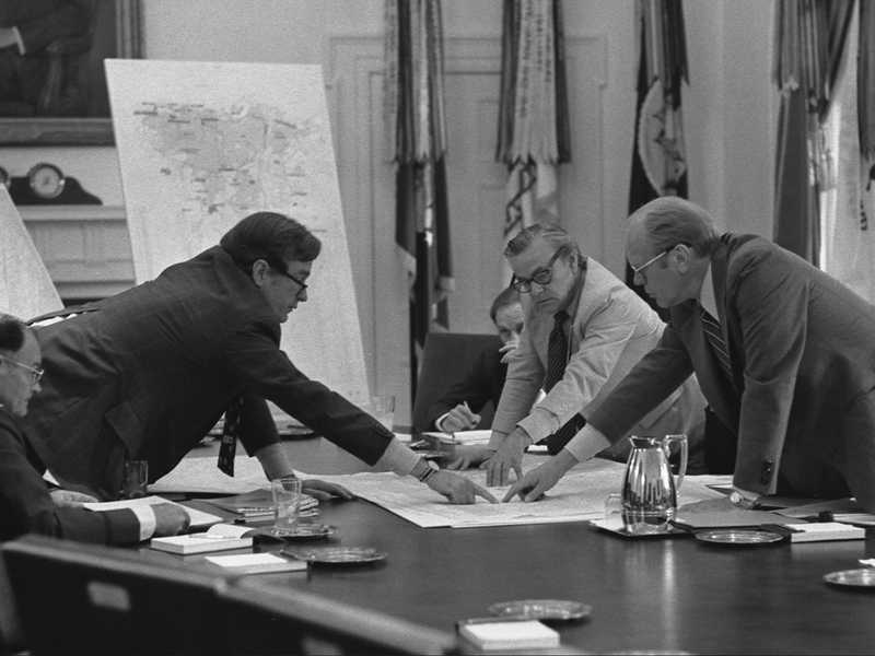 Men discussing around a table pointing to a piece of paper on the table between them.