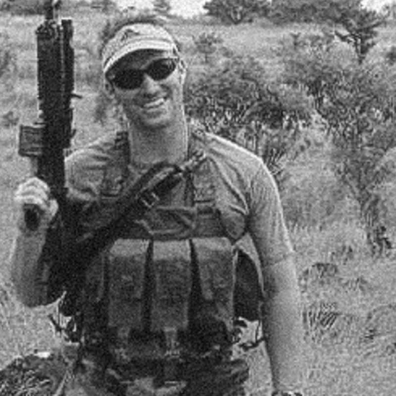 A photo of Glen A. Doherty in a military outfit and sunglasses, standing in greenery and holding a gun.