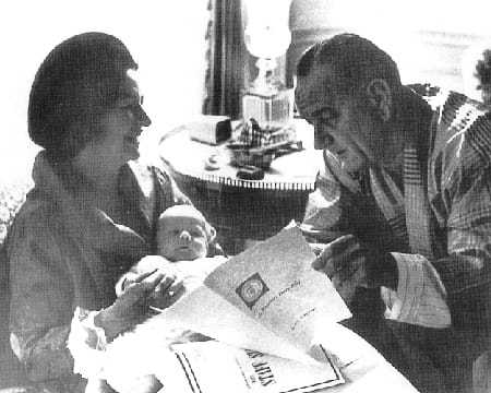 FDR reading the PDB beside his wife and baby.