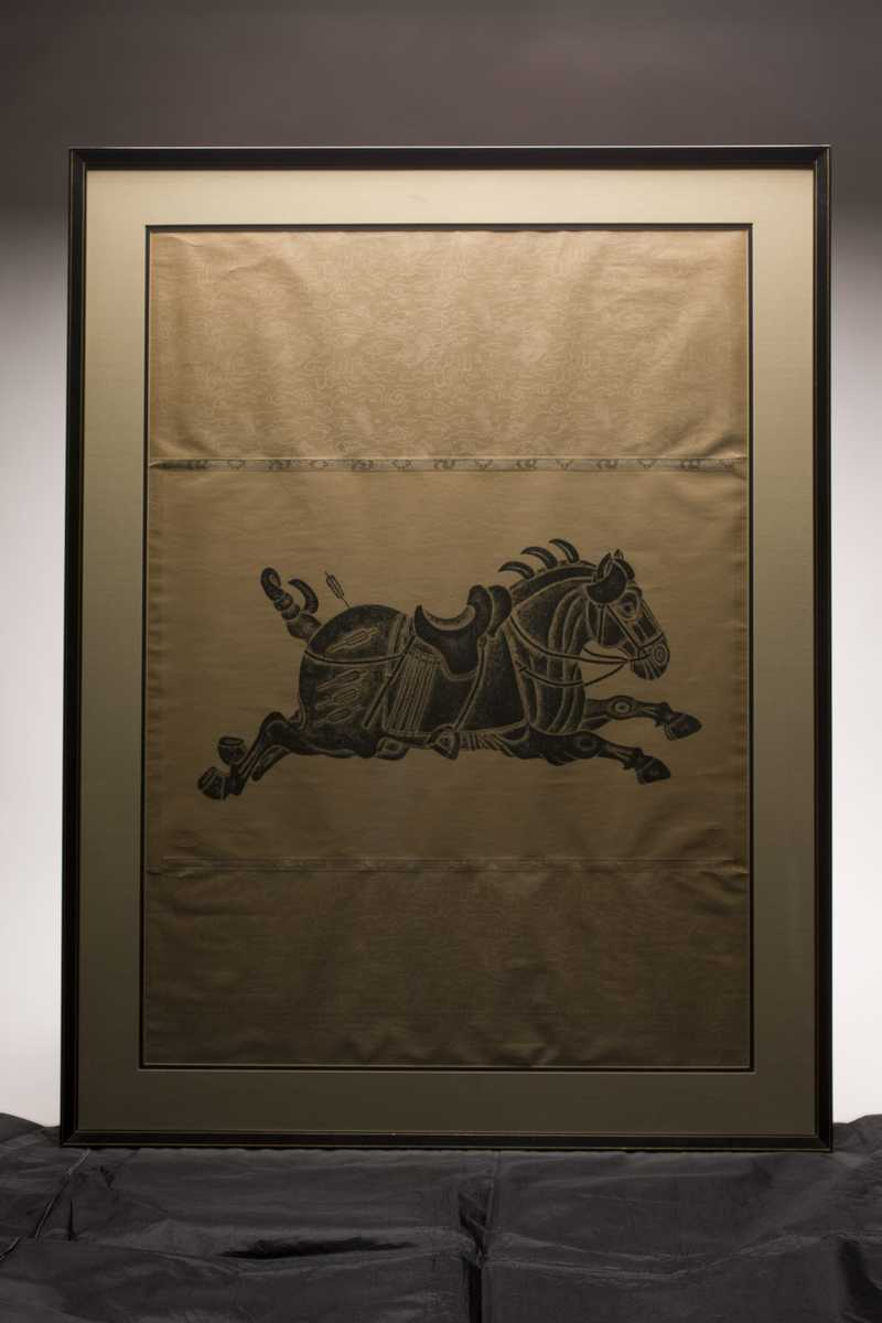 A framed print of a horse mid stride with a saddle and tack