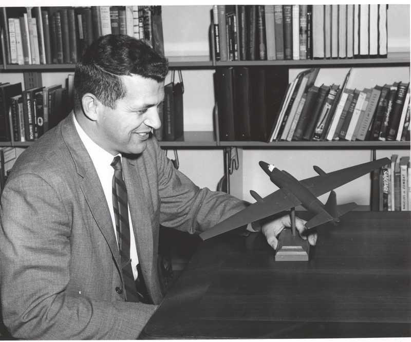 Francis Gary Powers holding a model plane in front of bookshelves.