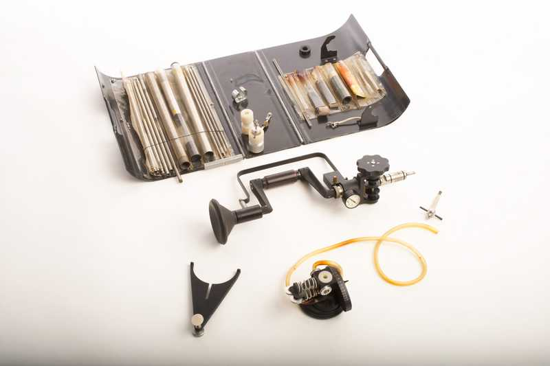 A drill with a hand crank, surrounded by drill bits and other parts