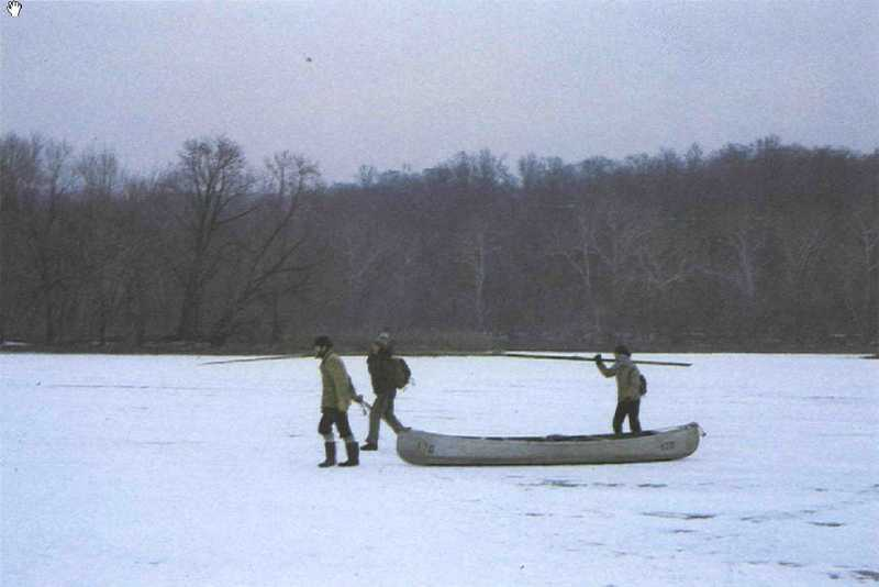Three men dragging a canoe in the snow.