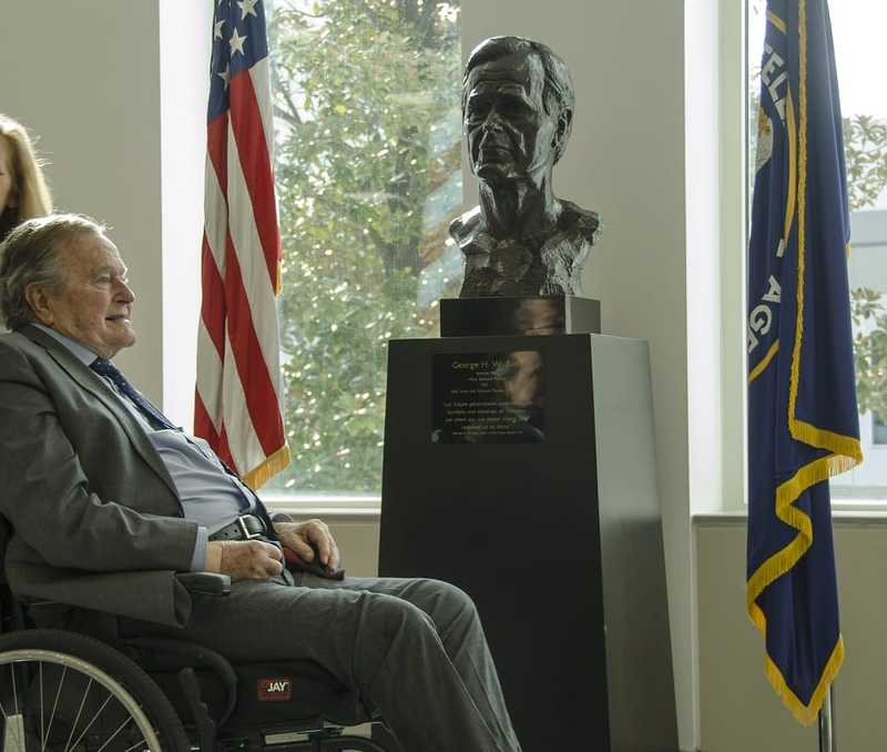 Bush, in a wheelchair, smiling at his bust statue sitting between the American glad and the CIA flag.