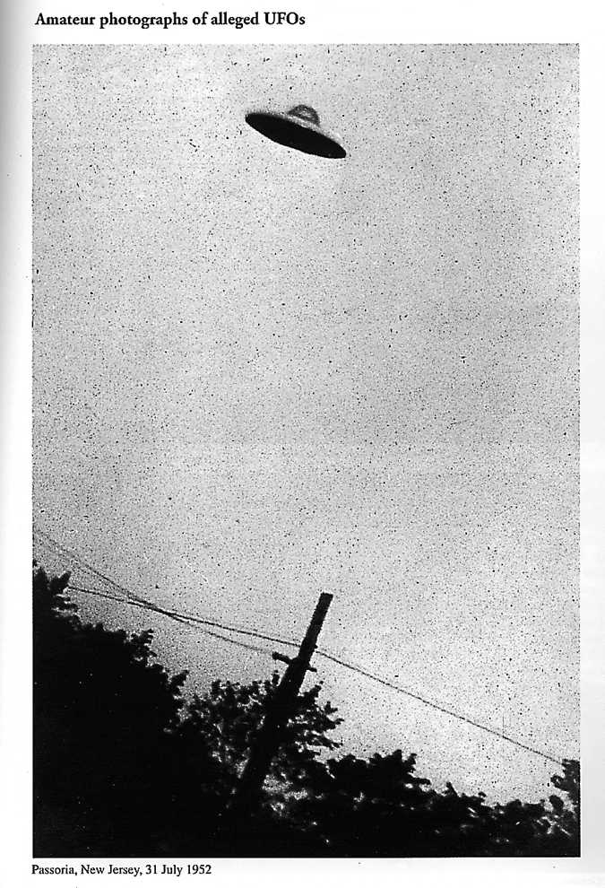 A black and white photograph of a small UFO flying atop the silhouette of trees and a powerline.
