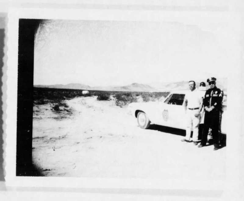 A blurry black and white photograph of a police officer and man standing outside a car.