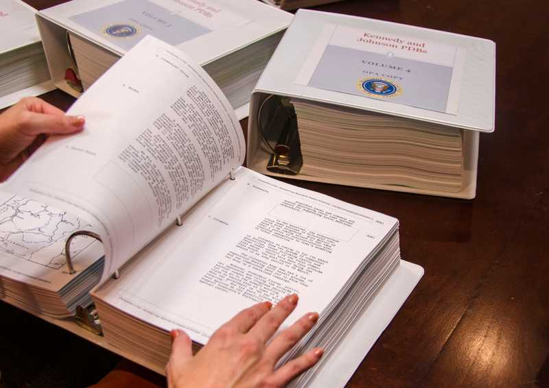 Close-up of hands flipping through large binders of documents with two other binders in the background.
