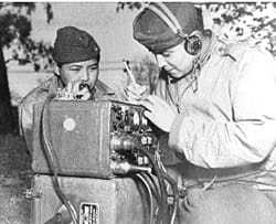 Two men huddled around a radio device.