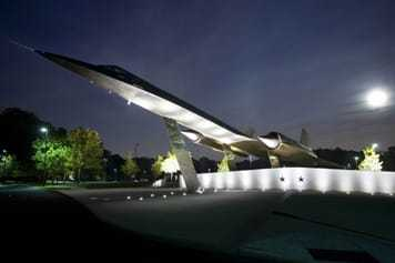 A retired A-12 Oxcart mounted on the ground, lit from beneath at night.