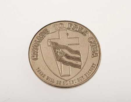 A silver coin with a crest and the phrases,