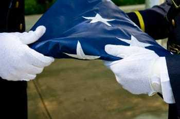 Two gloved hands holding a folded American flag.
