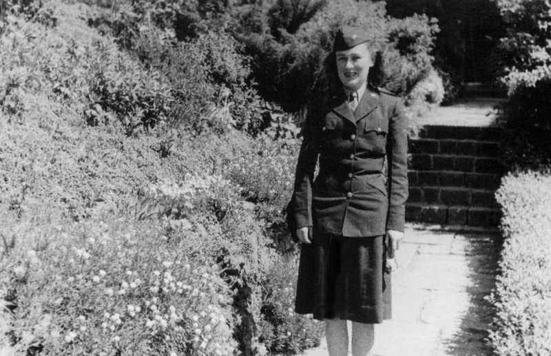 A black and white photograph of Burrell in uniform standing on a path by bushes.