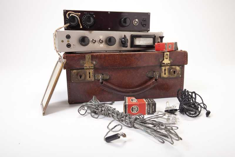 A radio composed of a brown suitcase, transmitter, receiver, frequency card, radium vacuum tube boxes, vacuum tube, and gray and black cords.