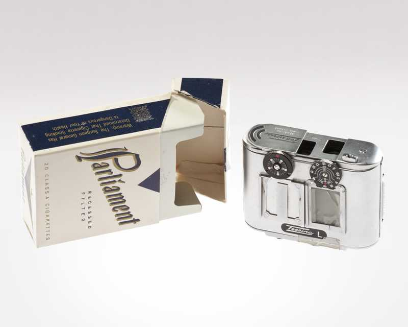 An empty box of Parliament cigarettes next to a smaller film camera with a silver metal exterior