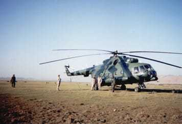 A helicopter landed on a large flat area, surrounded by several people.