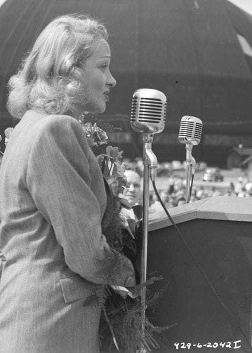 A sideview of Marlene Dietrich as she sings into a tall microphone in front of a podium.