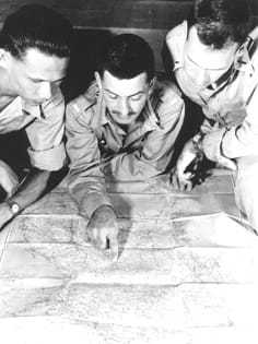 Three CIA field officers study a map.