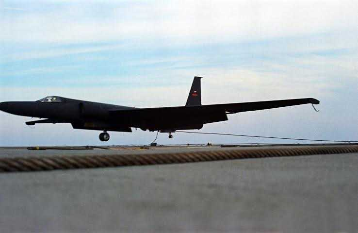 A U-2 aircraft just before landing on the tarmac on a blue sky day.
