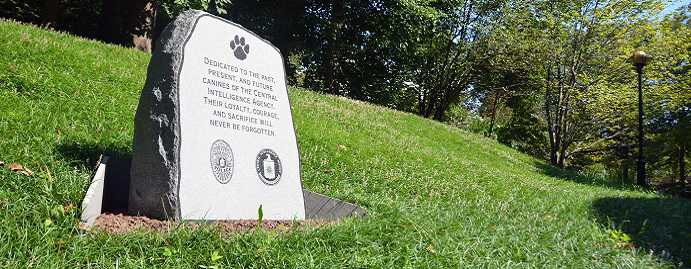 A color photograph of a small tombstone memorial in dedication to the past, present, and future canines of the CIA. A paw is imprinted at the top with the CIA logo below.