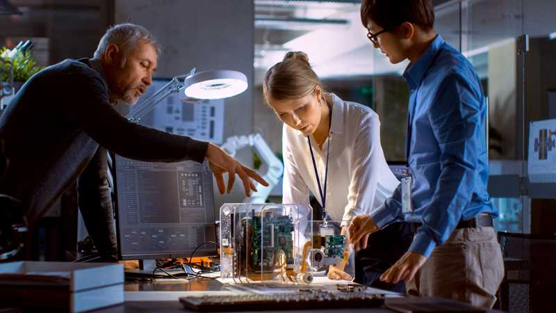 Three professionals standing around a complex mechanical device on a table.