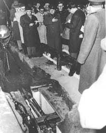 A collection of Soviet officials standing next to a hole in the ground exposing an underground tunnel.