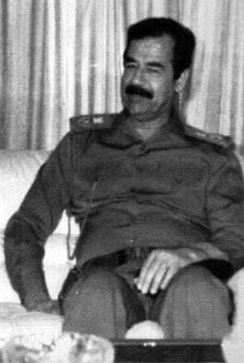 Image of Saddam Hussein sitting on a couch in military garb.