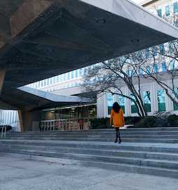 A woman in an orange coat walking up the steps outside CIA Headquarters