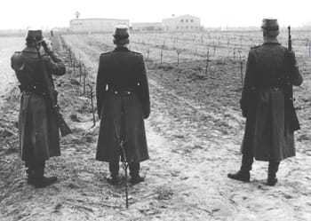 Three East German Police overlooking a field on the compound.