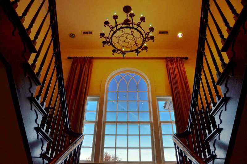 An upward looking shot of a large window and the chandelier at the entrance of the manor.