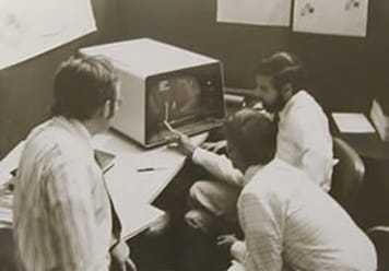 Image of employees gathered around an old computer.
