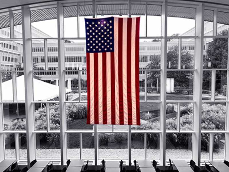 U.S. flag hanging in front of large windows in the CIA headquarters
