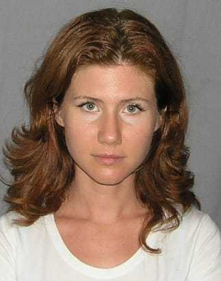 Headshot of a female Russian spy with long red hair.