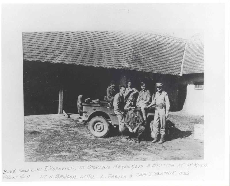 A faded black and white image of a group of men sitting on a car outside of a building.