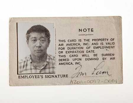 The reverse side of the Air America ID Card, with a picture and signature of Tom Lum.