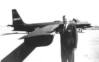 Man in suit standing beside a U-2 resting his arm on the wing.