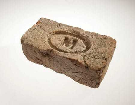 A damaged brick with an engraved oval with an