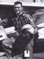 A black and white photograph of Gary with helmet in hand by a U-2.