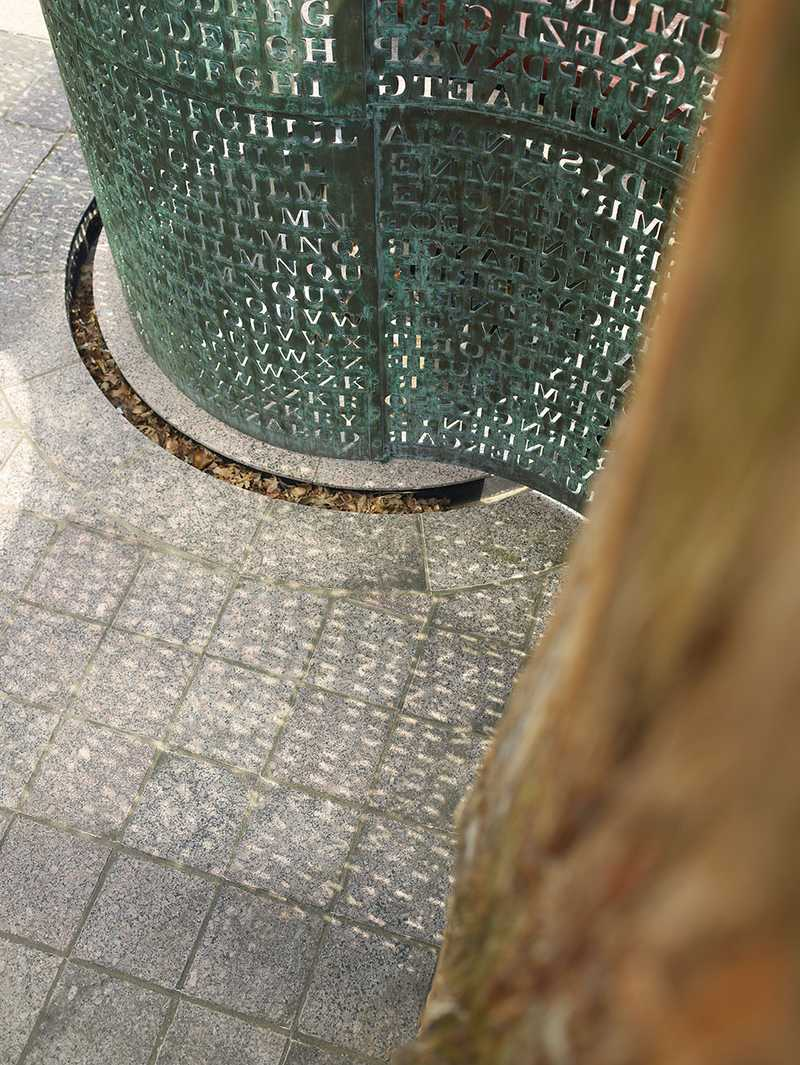 A shot looking downward at the base of the encircled copper screen with an indented ring in the ground collecting leaves and rainwater.